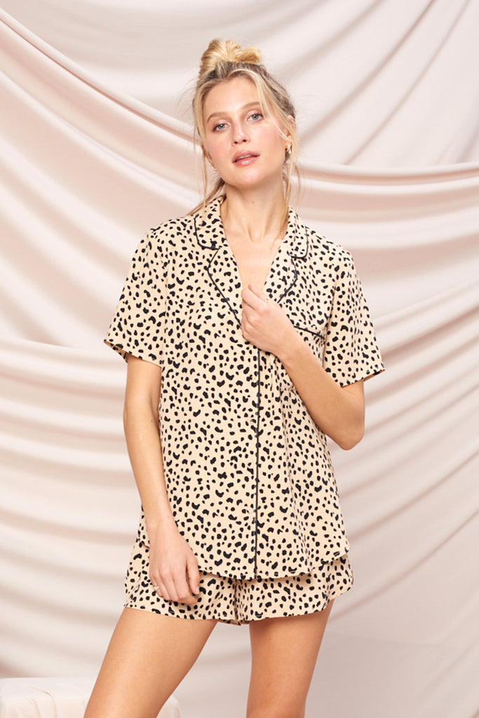 A woman wearing a sand leopard PJ set.