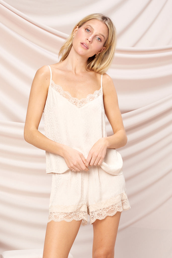 A woman wearing a beige satin ditsy animal print PJ set with lace trim detail at neck and hem.