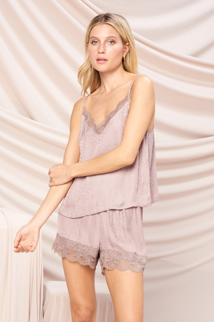 A woman wearing a mauve satin ditsy animal print PJ set with lace trim detail at neck and hem.