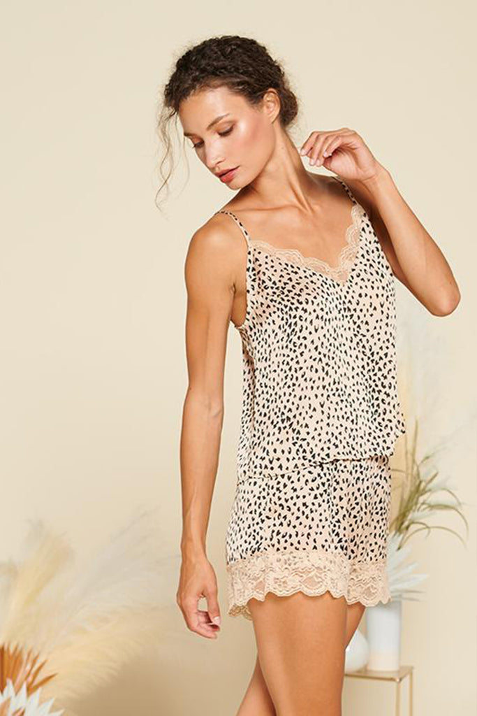 A woman wearing a beige leopard PJ set with lace detail on neckline and bottom hem.