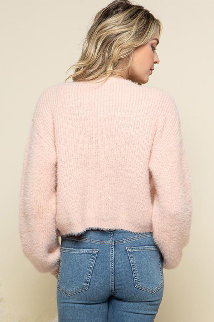 A woman wearing a mauve fuzzy sweater two piece cardigan set.