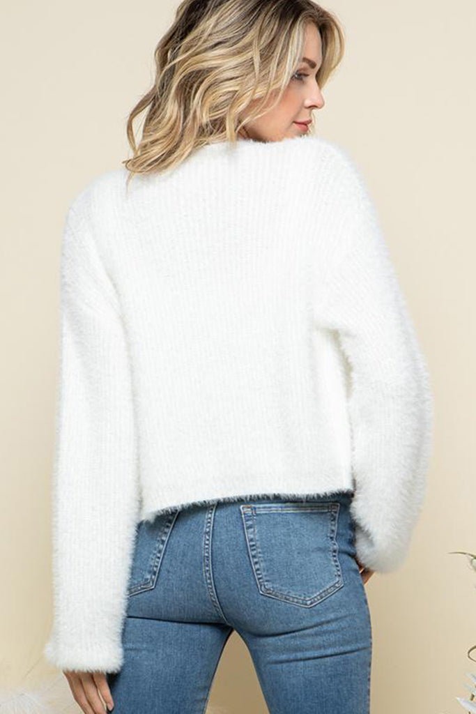 A woman wearing an ivory fuzzy sweater two piece cardigan set.