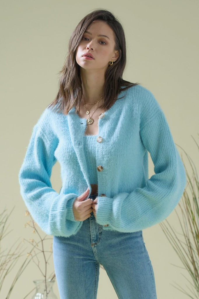 A woman wearing a light blue fuzzy sweater two piece cardigan set.