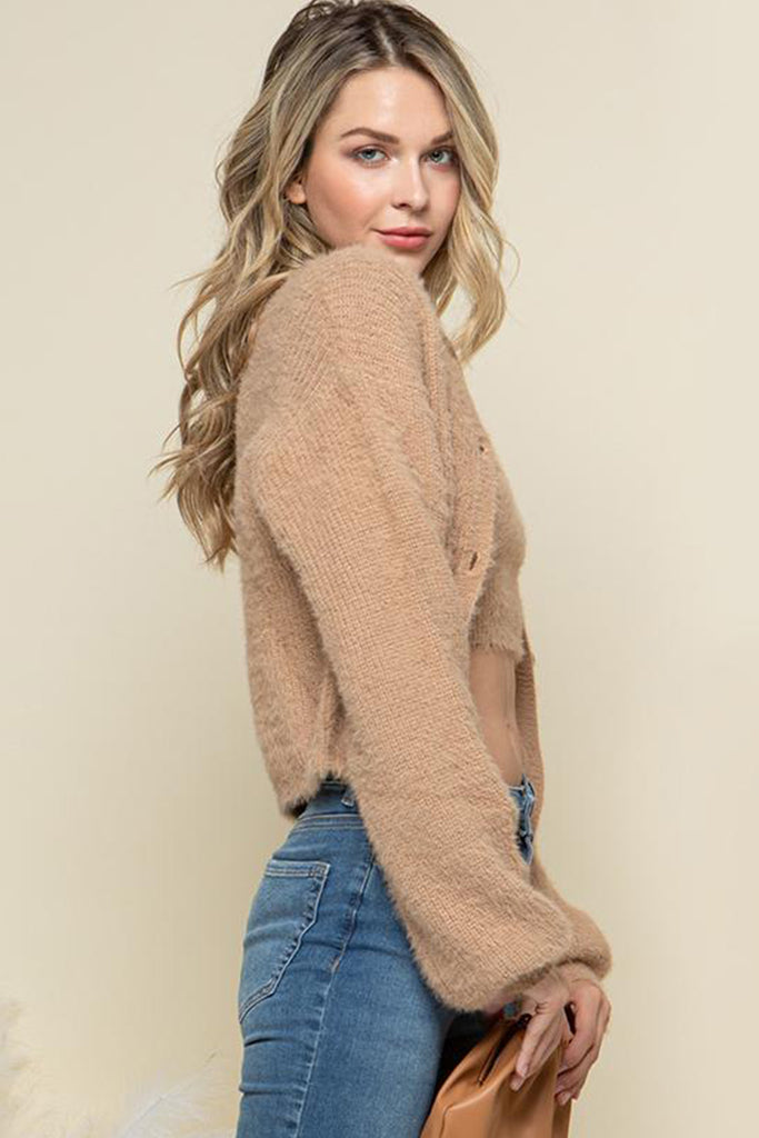 A woman wearing a camel fuzzy sweater two piece cardigan set.