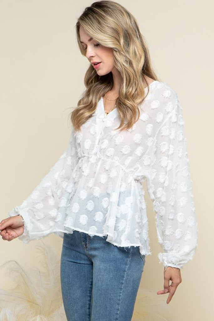 A woman wearing an off white Swiss dot peplum blouse.