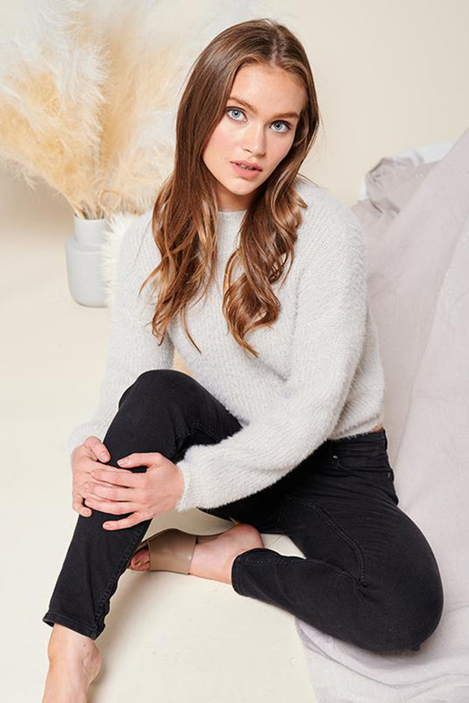A woman wearing a light grey mock neck fuzzy ribbed knit sweater.