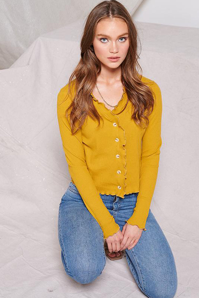 A woman wearing a mustard ribbed knit cardigan with merrow edges.