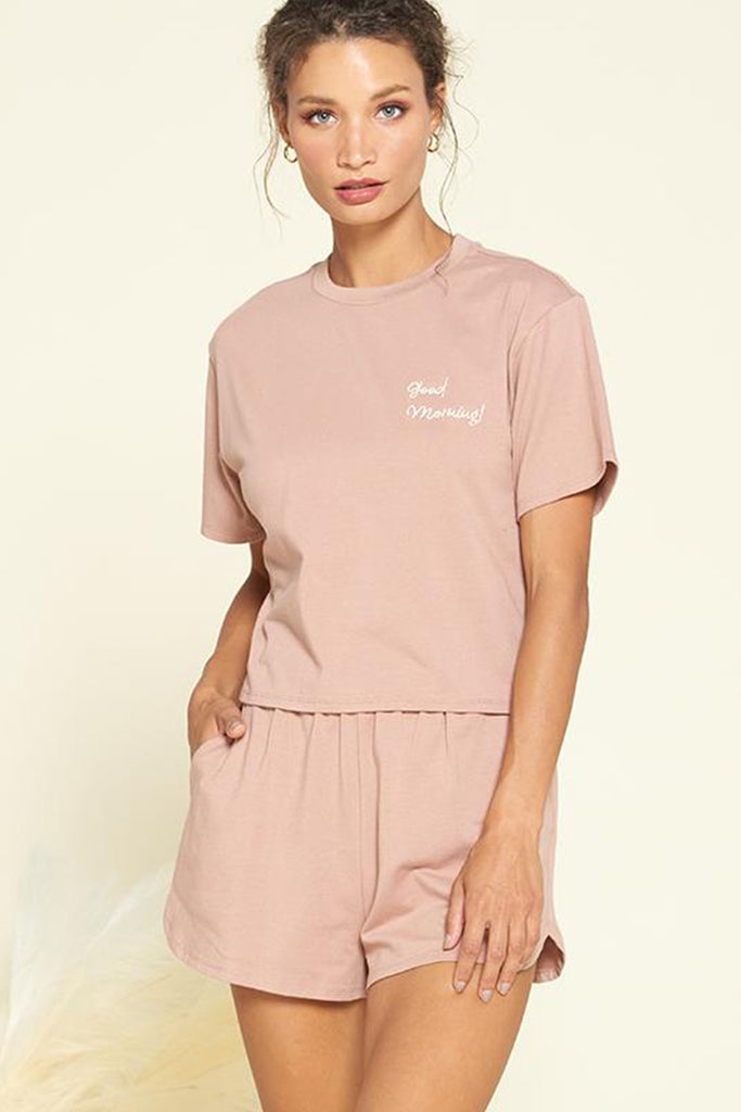 "A woman wearing a ""good morning!"" embroidered PJ set in mauve."