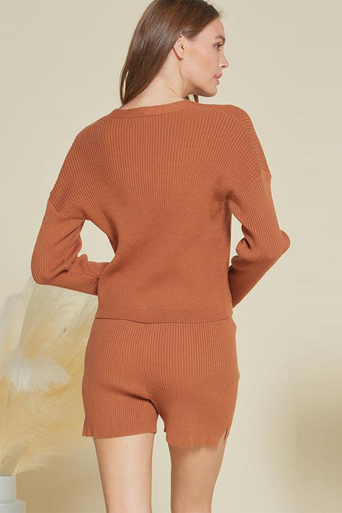 A woman wearing a rust rib knitted sweater two piece set.