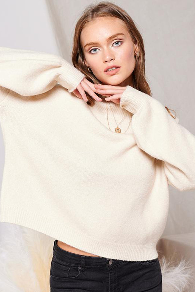 A woman wearing an ivory turtleneck sweater.