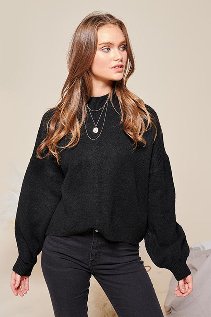 A woman wearing a black turtleneck sweater.