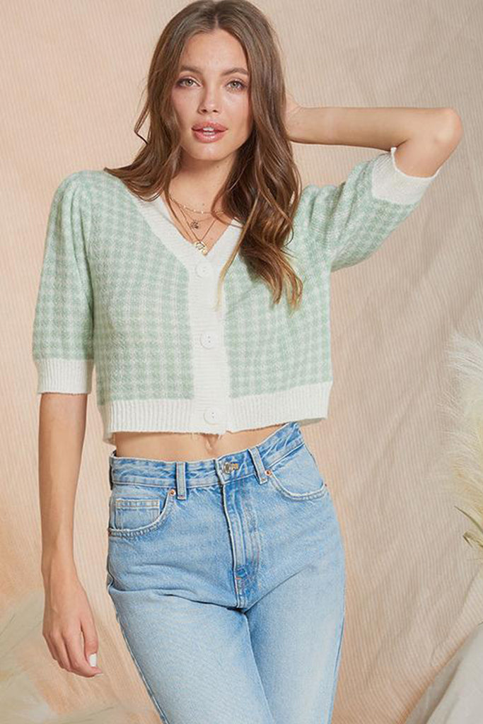 A woman wearing a mint gingham puff sleeve sweater top.