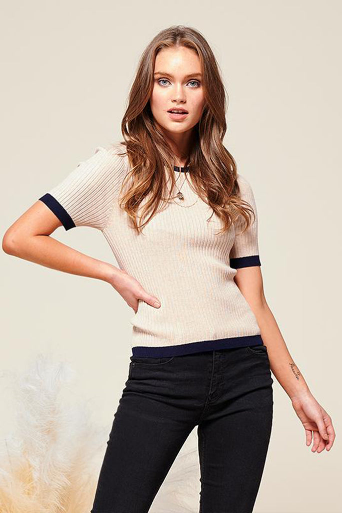 A woman wearing an oatmeal short sleeve contrast knit top.