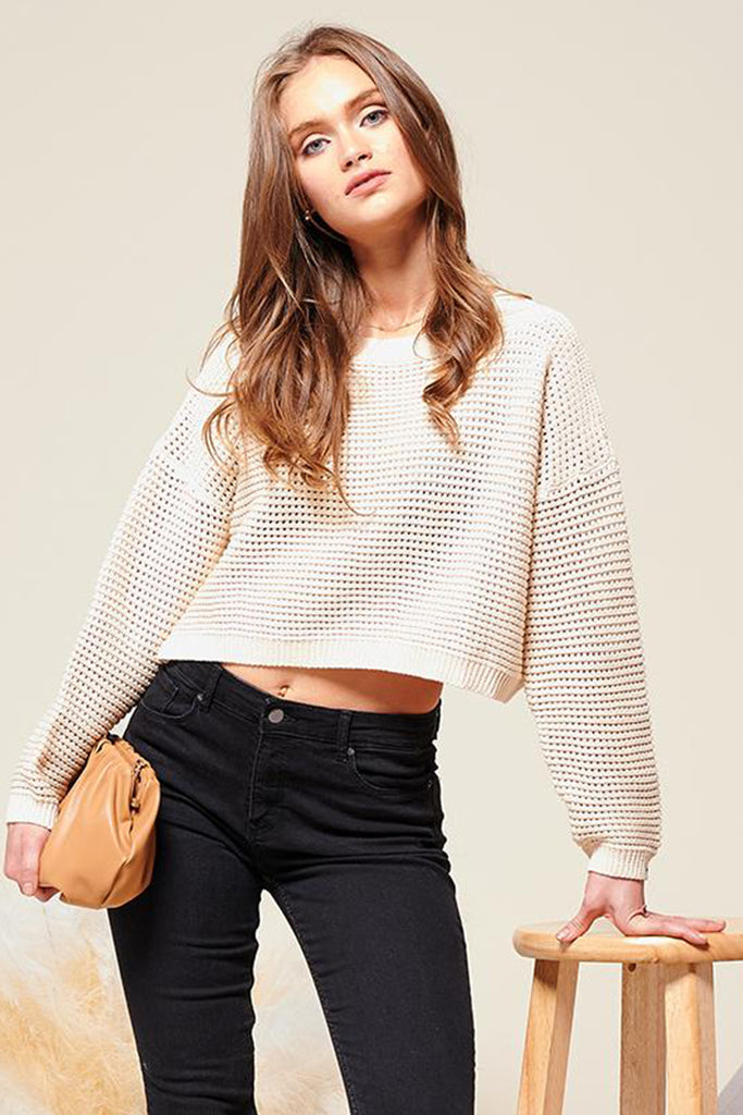 A woman wearing a cream cropped fishnet knitted sweater top.