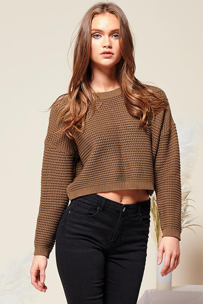A woman wearing an olive cropped fishnet knitted sweater top.
