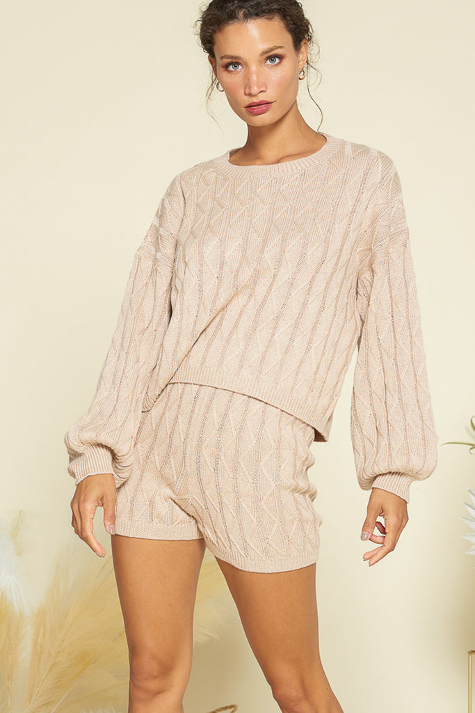 A woman wearing a taupe sweater loungewear two piece set.