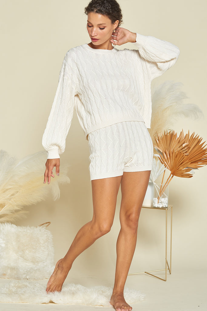 A woman wearing an ivory sweater loungewear two piece set.