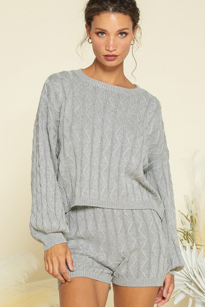 A woman wearing a heather grey sweater loungewear two piece set.