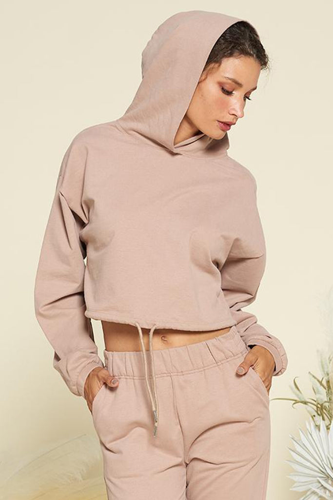 A woman wearing a mocha soft brushed terry cropped hoodie with adjustable drawstrings on waist. Pair it with matching loungewear pants.