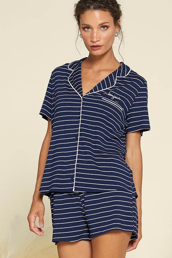 "A woman wearing a navy stripe PJ set with ""bonjour"" embroidered on chest."