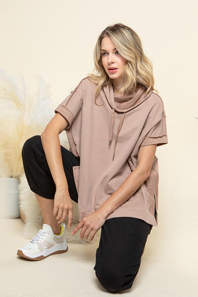 A woman wearing a mocha cowl neck with adjustable drawstring lounge top.