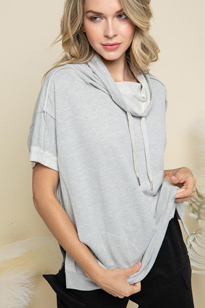 A woman wearing a heather grey cowl neck with adjustable drawstring lounge top.