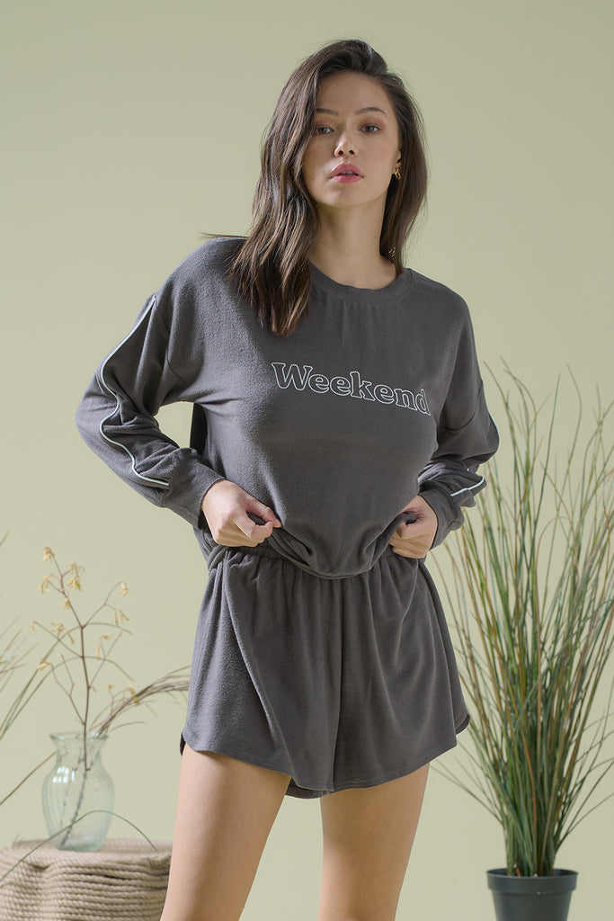A woman wearing 'Weekend' embroidered terrycloth lounge set with piping at side seam in charcoal color.