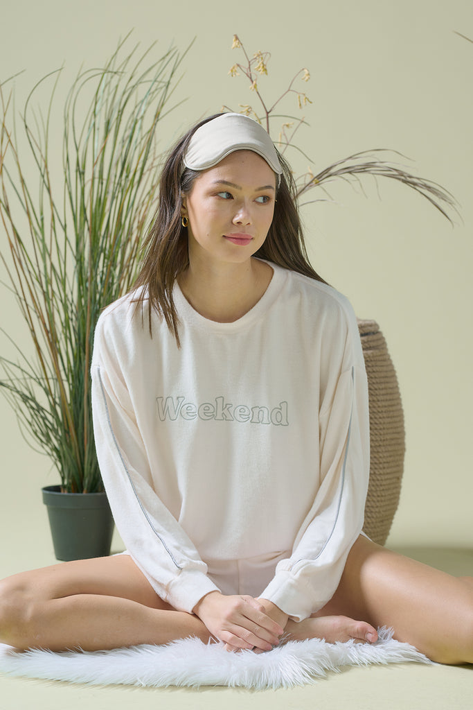 A woman wearing 'Weekend' embroidered terrycloth lounge set with piping at side seam in cream color.