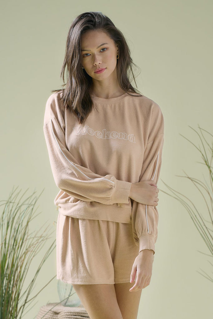 A woman wearing 'Weekend' embroidered terrycloth lounge set in sand colorA woman wearing 'Weekend' embroidered terrycloth lounge set with piping at side seam in sand color.