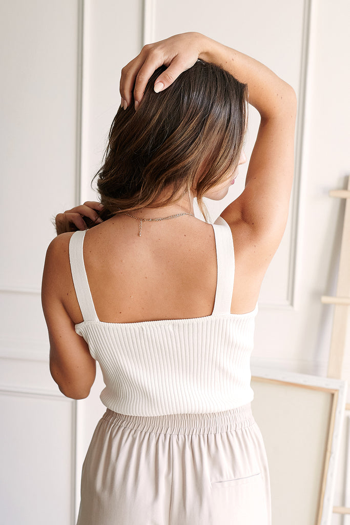 A woman wearing an ivory knitted bustier top.