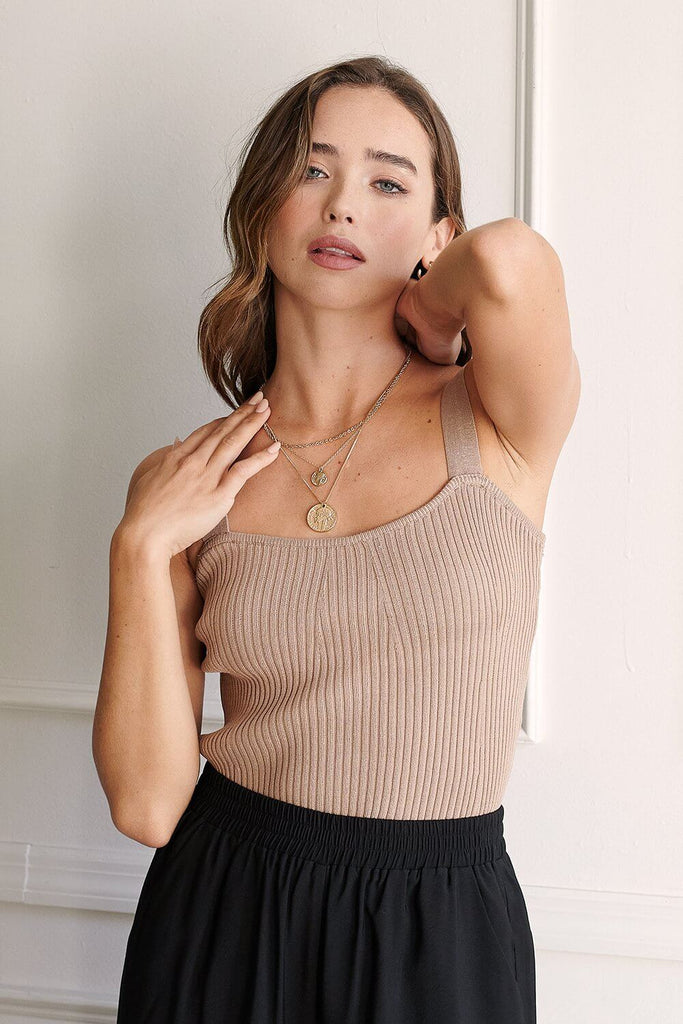 A woman wearing a sand knitted bustier top.