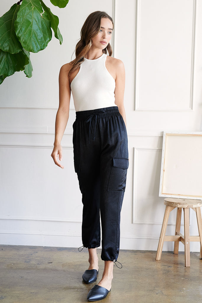 A woman wearing an ivory rib racer tank top and a black utility satin jogger pants.