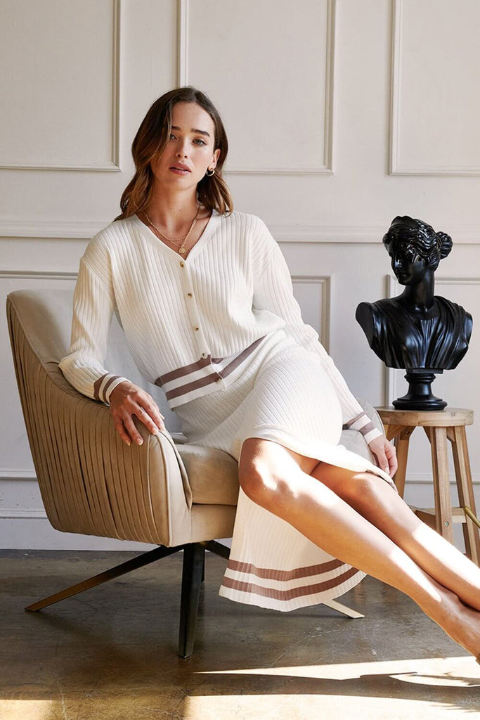 A woman wearing an ivory striped hem knit cardigan skirt set.