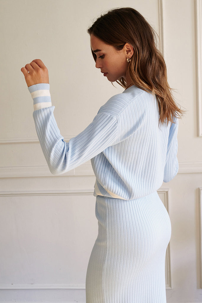 A woman wearing a light blue striped hem knit cardigan skirt set.