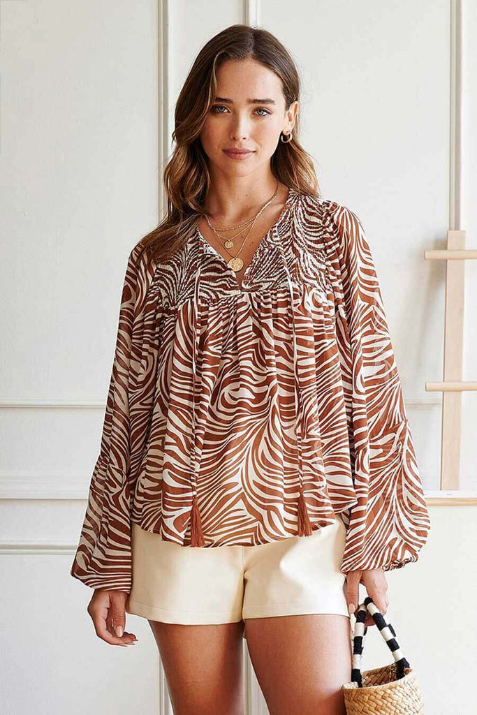 A woman wearing a brown zebra printed blouse with tassel trim.