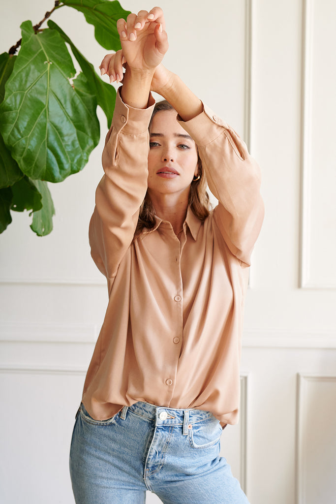 A woman wearing a sand button front satin shirt.