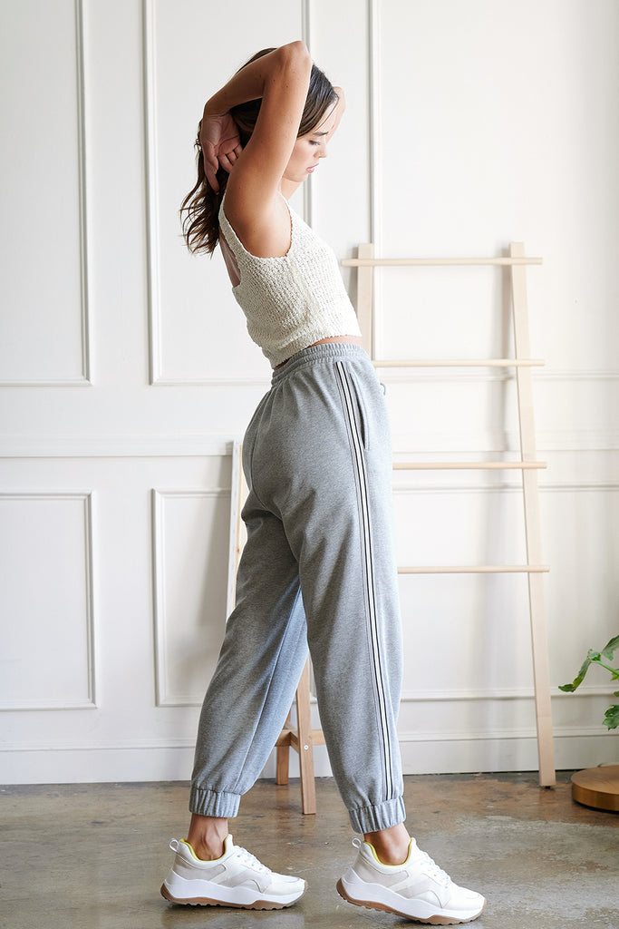 A woman wearing an ivory knitted tank top and a heather grey boyfriend jogger pants with side stripe trim tape detail.