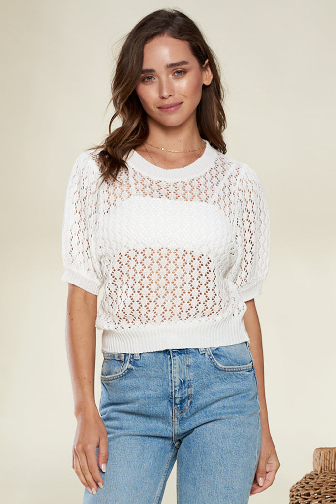 A woman wearing an ivory honeycomb see-through knit top.