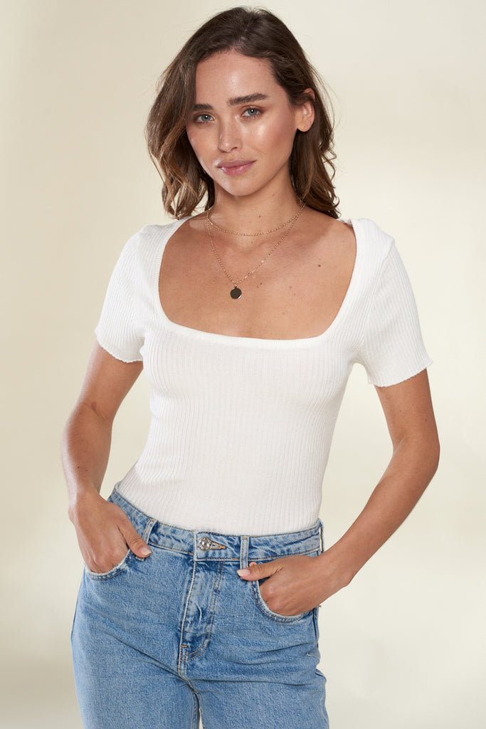 A woman wearing an ivory square-neck ribbed knit top.
