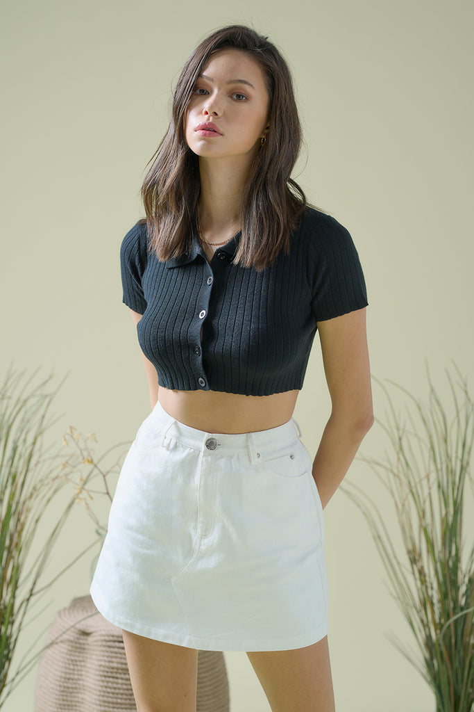 A woman wearing a black cropped knit top and ivory canvas mini skirt.