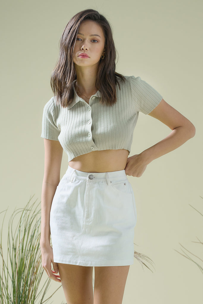 A woman wearing a sage cropped knit top and an ivory canvas mini skirt.