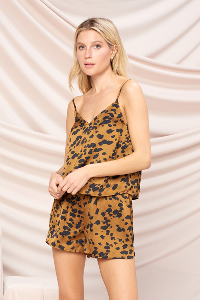 A woman wearing a brown leopard camisole PJ set with back tie detail.