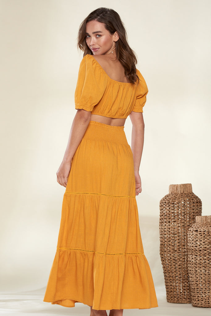 Back side of a marigold short puff sleeve top and skirt two-piece set.