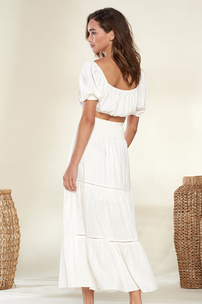 Back side of an ivory short puff sleeve top and skirt two-piece set.