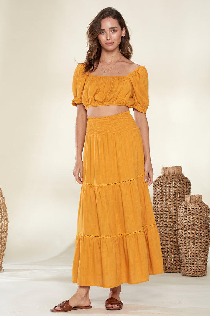 A woman wearing a marigold short puff sleeve top and skirt two-piece set.
