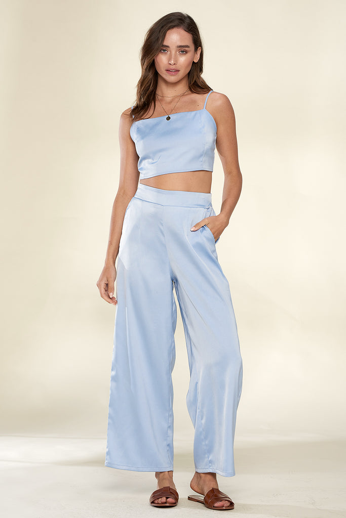 A woman wearing a light blue satin cropped top and wide-leg cropped length pants two piece set.