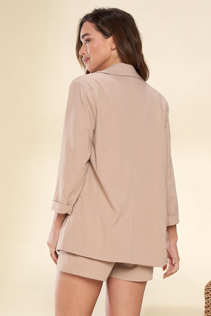 Back side of a tan lightweight blazer and shorts two piece set.