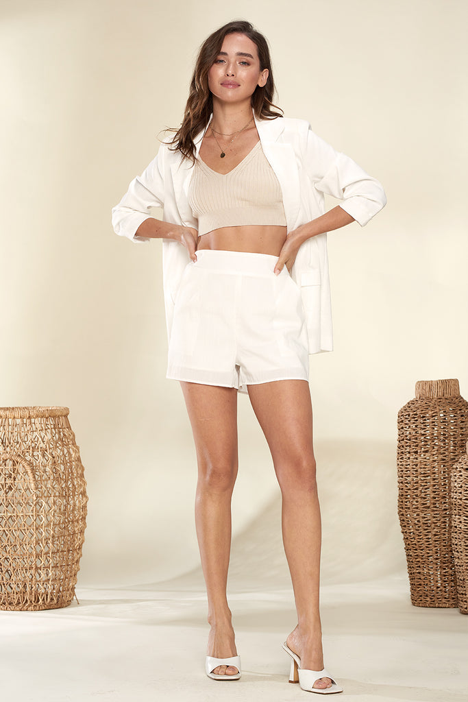 A woman wearing an ivory lightweight blazer and shorts two piece set.