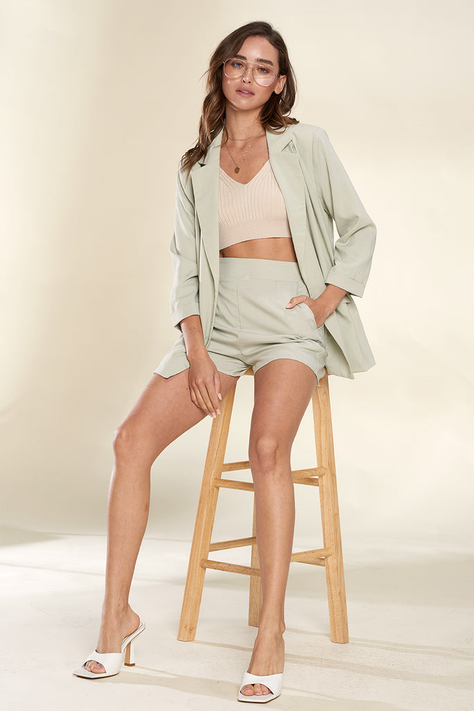 A woman wearing a sage lightweight blazer and shorts two piece set.