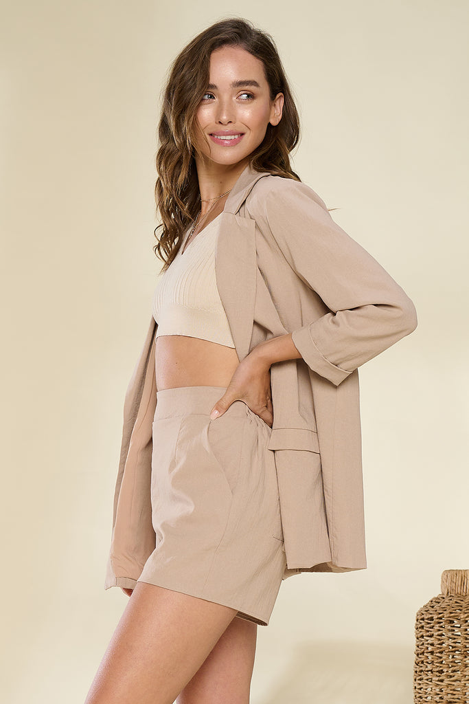 A woman wearing a tan lightweight blazer and shorts two piece set.
